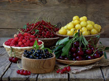 Fresh fruit and berries in baskets on wooden background. Red and black currants, raspberries, cherries, yellow plums royalty free stock images