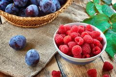 Fresh fruit and berries in baskets on wooden background - red and black currants raspberries, plums - rustic foto Royalty Free Stock Photography