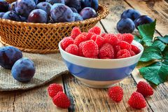Fresh fruit and berries in baskets on wooden background - red and black currants raspberries, plums - rustic foto Stock Image