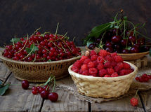 Fresh fruit and berries in baskets on wooden background. Red currants, raspberries, cherries royalty free stock image