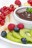 Fresh fruit and berries, chocolate sauce, selective focus. Close-up Stock Photo