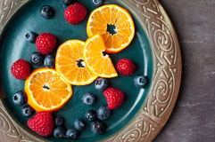 Fresh fruit and berries. Fresh cut slices of orange with strawberries and blueberries on a rustic plate on a slate stone table. A healthy snack or breakfast Royalty Free Stock Photos