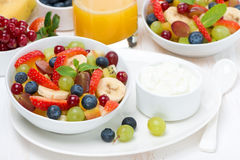 Fresh fruit and berry salad and cream for breakfast Royalty Free Stock Photo