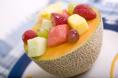 Fresh Fruit Bowl. Fresh Fruit in a Canteloupe Melon Bowl garnished with a Melon Sauce royalty free stock photo