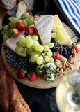 Fresh Fruit and Cheese Platter. Fresh fruit, berries and nuts on a cheese platter Royalty Free Stock Photography