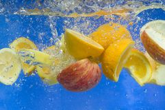 Fresh fruit falling in water Royalty Free Stock Images