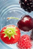 Fresh Fruit Floating in Sparkling Water. Overhead close Up of a selection of fresh fruit, floating on top of blue sparkling water. Includes strawberry, cherry Royalty Free Stock Photo