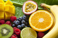 Fresh Fruit Food. A collection of fresh fruit including blueberries raspberries, orange, lime, banana, mango, passion fruit and kiwi fruit on a green banana leaf Stock Photo