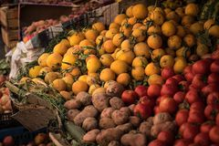 Fresh fruit at a fruit stand. Piles of fresh oranges, tomatoes and potatoes at an outdoor fruit stand in a souk in Marrakech. Red Royalty Free Stock Photo