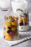 Fresh fruit in a glass jar and yogurt close up vertical Stock Images
