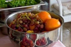 Fresh fruit grapes, orange in a silver bowl. Fresh greens, lettu Royalty Free Stock Image