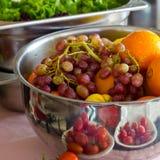 Fresh fruit grapes, orange in a silver bowl. Fresh greens, lettu Stock Photo