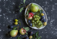 Fresh fruit - grapes, pears, apples, plums on a dark background Stock Photo