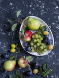 Fresh fruit - grapes, pears, apples, plums on a dark background Stock Photography