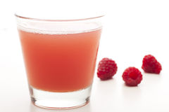 Fresh Fruit Juice. Glass of fresh fruit juice with three raspberries in the background Royalty Free Stock Photo
