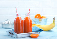Fresh fruit juice. In bottle and on a table Royalty Free Stock Photos