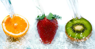 Fresh fruit jumping into water stock photos