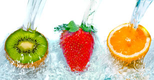 Fresh fruit jumping into water with a splash royalty free stock photography