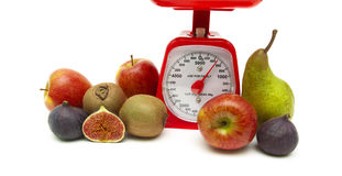 Fresh fruit and kitchen scale on white background Royalty Free Stock Photos