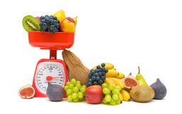 Fresh fruit and kitchen scales isolated on white background Stock Photos