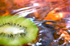 Fresh fruit, kiwi. Kiwi fruit on the water and a drop falling Royalty Free Stock Image