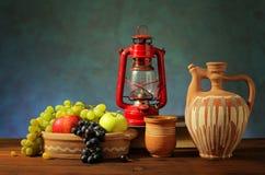 Fresh fruit, lantern and ceramic dishes Stock Images