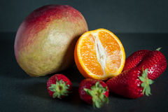 Fresh fruit (mango, orange, strawberries) on a dark background Royalty Free Stock Image