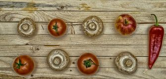 Fresh fruit. Mushrooms, tomatoes, peppers and Apple on a wooden table. Fresh fruit. Mushrooms, tomatoes, peppers and Apple on a wooden table Royalty Free Stock Images