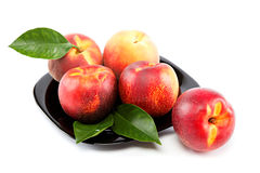Fresh fruit nectarines and peaches with green leaves. Stock Image