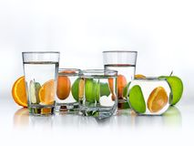Fresh fruit oranges and apples are located behind glasses with water on a white background stock photos