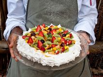 Fresh fruit pavlova on glass tray held by chef. Seasonal summer fruits on a meringue pavlova held by chef on glass plate with white dusting sugar falling gently royalty free stock image
