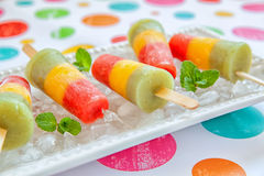 Fresh fruit popsicles with strawberry, mango, peach and kiwi. Homemade pureed fresh fruit popsicles with strawberry, mango, peach and kiwi Stock Images