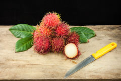 Fresh fruit rambutan on wood background from thailand and a knif Royalty Free Stock Photos