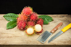 Fresh fruit rambutan on wood background from thailand and a knif Stock Photos