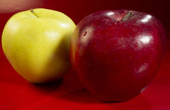 Fresh fruit. Red and golden apples on red table stock images