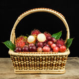 Fresh fruit red grapes and rambutan in basket on wood background.  Royalty Free Stock Photos