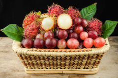 Fresh fruit red grapes and rambutan in basket on wood background.  Stock Photography