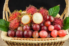 Fresh fruit red grapes and rambutan in basket on wood background.  Stock Image