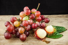 Fresh fruit red grapes and rambutan on wood background.  Royalty Free Stock Image