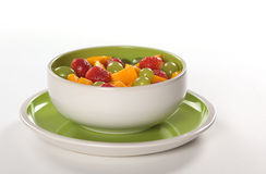 Fresh Fruit Salad. Healthy fresh fruit salad out of mango, strawberry and white grapes in green-white bowl photographed on white (Selective Focus, Focus on the Stock Photography