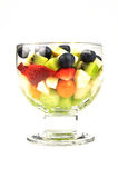 Fresh Fruit Salad. Close up of a bowl containing fresh fruit salad of blueberries, strawberries, melon, kiwi, apple and Physalis in front of a white background Stock Photo