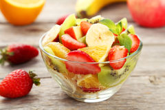 Fresh fruit salad in bowl on grey wooden background. Stock Photo