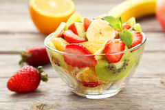 Fresh fruit salad in bowl on grey wooden background. Royalty Free Stock Photo