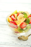 Fresh fruit salad in bowl on white wooden background. Stock Image