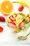 Fresh fruit salad in bowl on white wooden background. Stock Photos