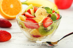 Fresh fruit salad in bowl on the white wooden background Stock Photos