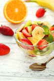 Fresh fruit salad in bowl on a white wooden background Royalty Free Stock Photography