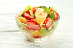 Fresh fruit salad in bowl on a white wooden background Royalty Free Stock Images