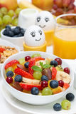Fresh fruit salad, cream, painted eggs for breakfast Royalty Free Stock Photo