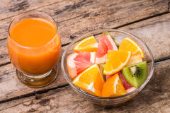 Fresh fruit salad with glass of juice. Fresh fruit salad with glass of apple and carrot juice on old wooden table. Eco food vitamins background Royalty Free Stock Image